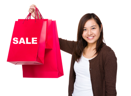 Asian woman holding with shopping bag and showing a word sale