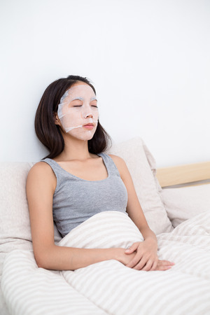 Woman sitting in bed with her mask sheet