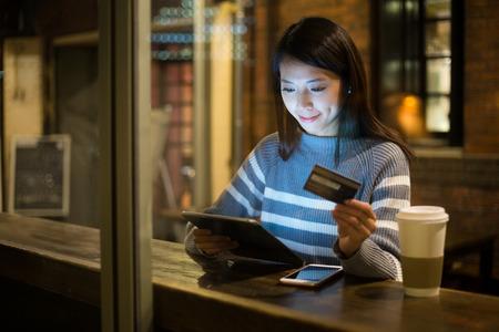 Foto de Young woman using credit card for paying on tablet - Imagen libre de derechos