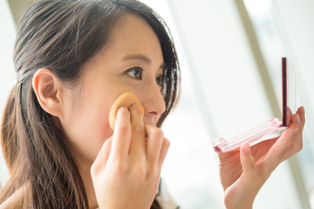 Photo pour Woman using powder to touch up on her face - image libre de droit