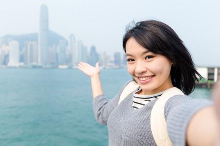 Photo pour Woman take selfie and showing the skyline of Hong Kong - image libre de droit