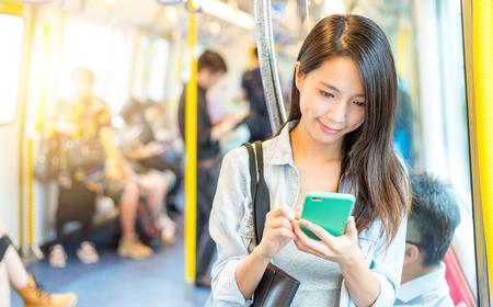 Foto de Woman working on mobile phone inside train compartment - Imagen libre de derechos