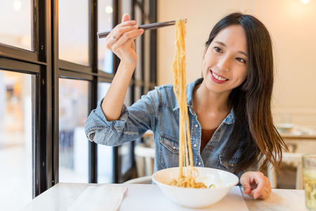 Foto de Asian Woman eating noodles in chinese restaurant - Imagen libre de derechos