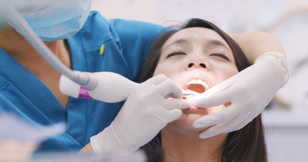 Photo pour Woman doing Scaling and root planing in dental clinic - image libre de droit