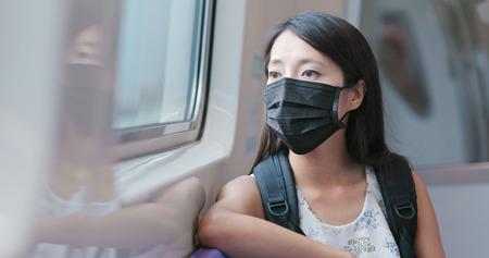 Photo pour Woman wearing protective mask and taking train - image libre de droit
