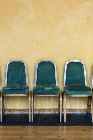 Photo pour Green chairs lined up against a yellow wall in a waiting area - image libre de droit