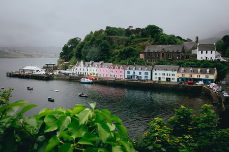 Photo pour The row of pastel coloured houses in Portree harbour in gloomy weather - image libre de droit