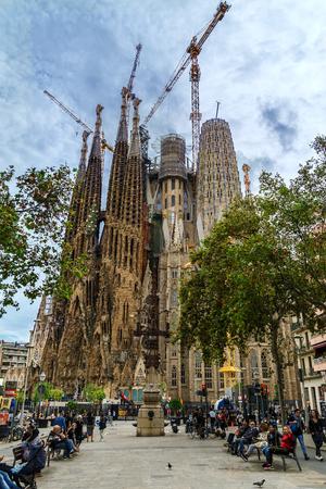Foto de BARCELONA, SPAIN - OCTOBER 10, 2018: View of Sagrada Familia cathedral with construction cranes from pedestrian street. - Imagen libre de derechos