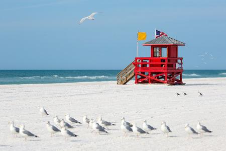 Photo pour Red wooden lifeguard hut on an empty morning beach - image libre de droit