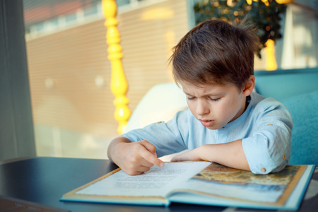 Photo pour Boring and tired little boy reading book for elementary school - image libre de droit