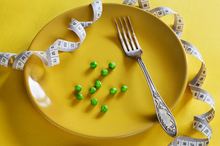 Photo for Horizontal photo of yellow plate with centimeter, peas and fork - Royalty Free Image