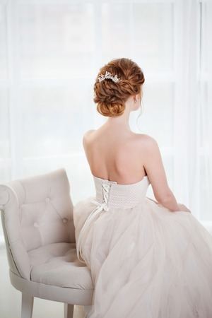 Photo for Beautiful red-haired bride sits in the chair, stylish hairstyle, back view. Young woman in luxurious wedding dress - Royalty Free Image