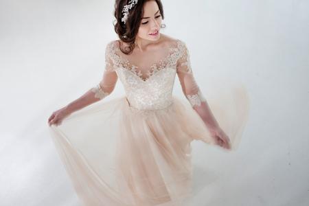 Foto de Dancing beautiful girl in a wedding dress. Bride in luxurious dress on a white background - Imagen libre de derechos