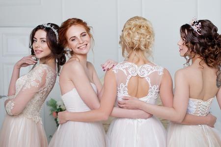 Foto de Bride in wedding salon. Four beautiful girl are in each others arms. Back, close-up lace skirts - Imagen libre de derechos
