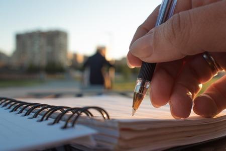 Photo pour Close-up, writing in a notebook, develop a plan of action - image libre de droit