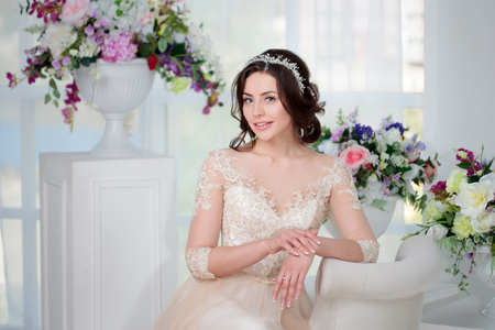 Photo pour Portrait of beautiful girl in a luxurious wedding dress. Interior decorated with flowers - image libre de droit
