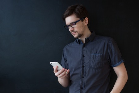 Photo for Young adult guy in a grey shirt uses a smartphone. Business portrait on textured black background - Royalty Free Image