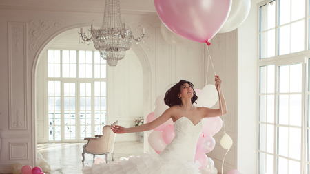 Photo pour Young woman in wedding dress in luxury interior flies on pink and white balloons. Charming young bride brunette with short haircut in stylish Quinceanera dresses. - image libre de droit