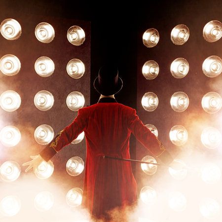 Photo for Showman. Young male entertainer, presenter or actor on stage. Back, arms to sides, smoke on background of spotlight - Royalty Free Image
