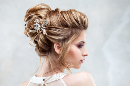 Foto de Young beautiful bride with an elegant high hairdo. Wedding hairstyle with the accessory in her hair. Close-up portrait on light background - Imagen libre de derechos