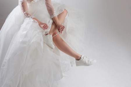Photo pour The girl in a magnificent wedding dress and white sneakers, legs close-up. Runaway bride - image libre de droit