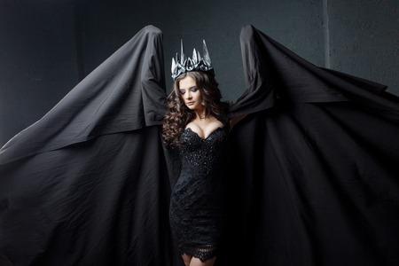 Photo pour Portrait of a Gothic Princess. Beautiful young brunette woman in metal crown and black cloak. Mystical image - image libre de droit