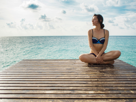 Photo for Young woman sitting in lotus pose on a background of beautiful sky and sea. Relax on a tropical island, maldivian resort - Royalty Free Image