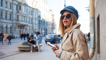 Foto de Cute fashionable girl uses smartphone to navigate the city, watch the map of area in the phone. Young woman with phone on the street, lifestyle - Imagen libre de derechos