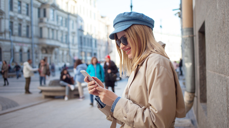 Foto de Cute fashionable girl uses apps in phone, shopping and banking. Young woman with phone on the street, lifestyle - Imagen libre de derechos