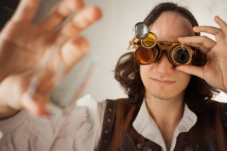 Photo pour Steampunk style researcher mechanist of the monocle with a large number of lenses looking at something. Young man in leather vest and vintage style - image libre de droit
