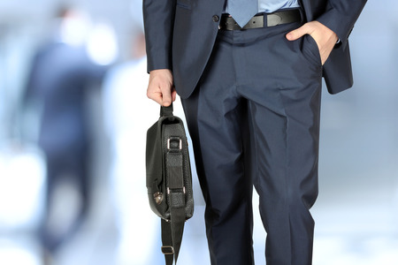 Businessman walking and holding  a  leather briefcase in his hand. Modern city behind
