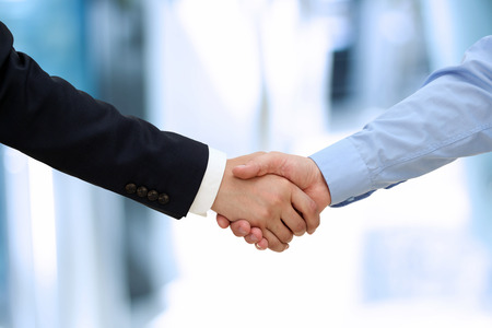 Photo pour Close-up image of a firm handshake  between two colleagues in office. - image libre de droit