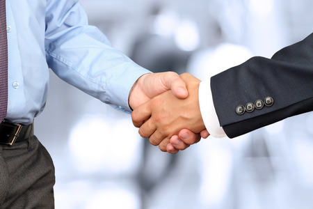Photo for The Close-up image of a firm handshake between two colleagues in office. - Royalty Free Image