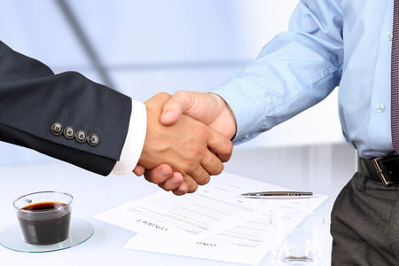 Foto de The Close-up image of a firm handshake between two colleagues under contract - Imagen libre de derechos