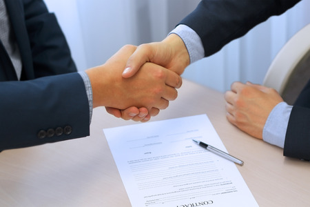 Photo pour Close-up image of a firm handshake between two colleagues after signing a contract - image libre de droit