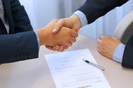 Foto de Close-up image of a firm handshake between two colleagues after signing a contract - Imagen libre de derechos