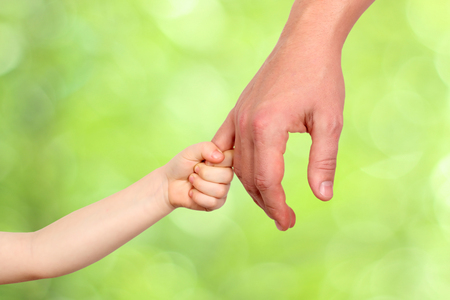 Foto de a father  holds the hand of a small child on a green  background - Imagen libre de derechos