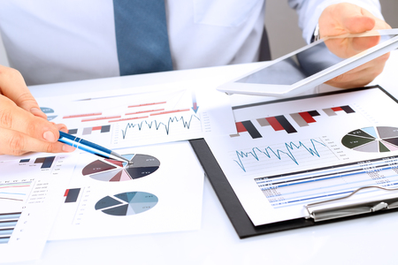 Foto de Close-up Of Businessman Analyzing Graph On Digital Tablet - Imagen libre de derechos