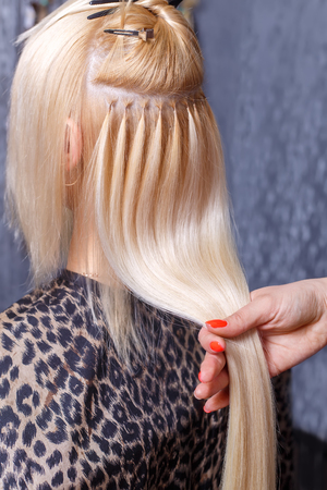 Photo pour Hair extensions procedure. Hairdresser does hair extensions to young girl, blonde in a beauty salon. Selective focus. - image libre de droit