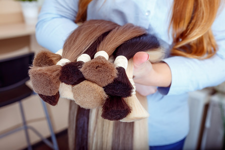 Foto de Woman holds hair extension equipment of natural hair. hair samples of different colors - Imagen libre de derechos