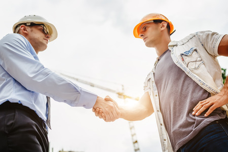 Photo pour Architect engineer shaking hands other hand at construction site.  Business teamwork, cooperation, success collaboration concept - image libre de droit