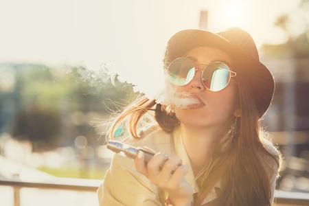 Foto de Pretty young hipster woman in black hat vape ecig, vaping device at the sunset. Toned image. - Imagen libre de derechos