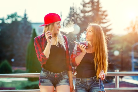 Photo pour Two women vaping outdoor. The evening sunset over the city. Toned image. - image libre de droit