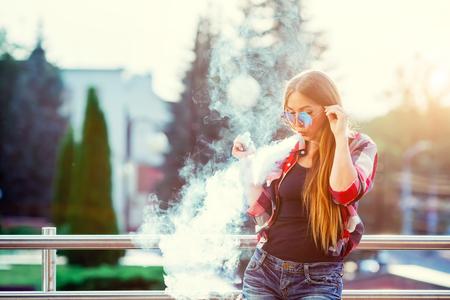 Foto de Young pretty hipster woman vaping and releases a cloud of vapor. The evening sunset over the city. Toned image. - Imagen libre de derechos