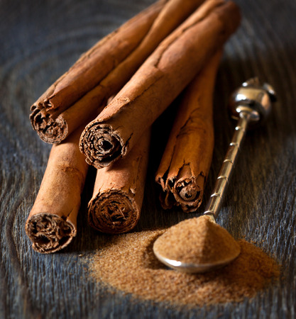 Photo for Cinnamon sticks and cinnamon powder on silver spoon close up. - Royalty Free Image