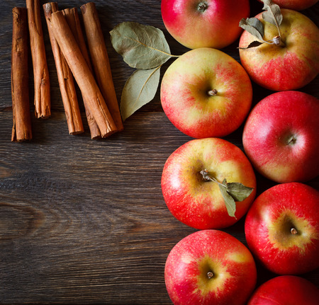 Photo for Fresh ripe red apples and cinnamon sticks on wooden background. - Royalty Free Image