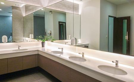 Foto de Faucets with washbasin and big mirror in public restroom - Imagen libre de derechos