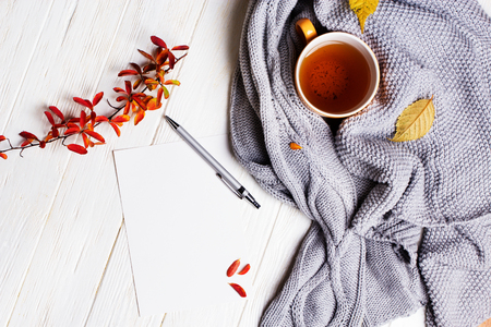 Photo pour Autumn flatlay on wooden backdrop with a cup of tea and  fallen dry yellow and red leaves. Free space for text. Cozy home concept - image libre de droit