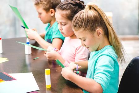 Photo pour Schoolchildren sitting at table and making applique - image libre de droit