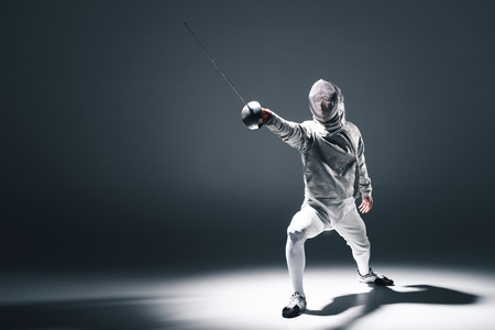 Photo for Professional fencer in fencing mask with rapier standing in position - Royalty Free Image